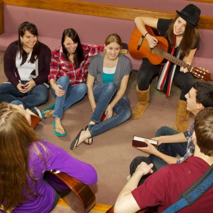 Eight teen friends play guitar and worship together in church setting
