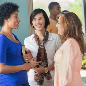 Diverse girl friends talking in lobby of church after service