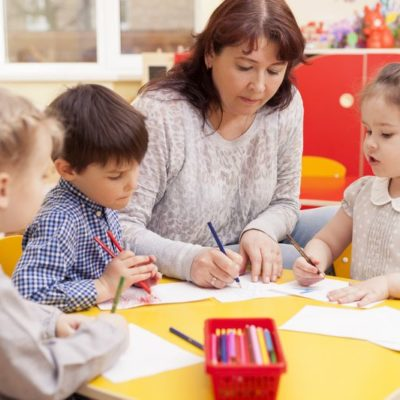 Kindergarten teacher, beautiful, mature caucasian woman, brown hair, teaches pupils drawing. Two little girls and a boy.