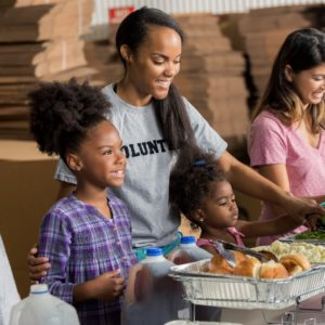 African American mother and her two daughters serve meals to the homeless with their diverse family.